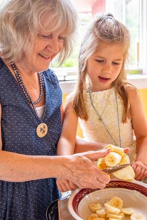 An older white woman and a white child in a brightly lit kitchen slicing bananas